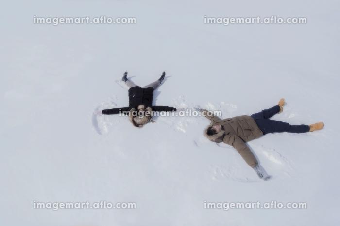 雪の上に寝転んで天使の羽根を作るカップルの販売画像