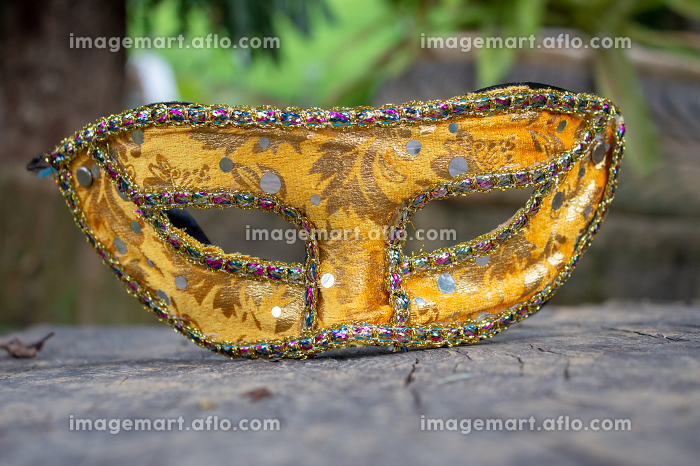 Carnival mask from Brazil, resting on a wooden boardの販売画像