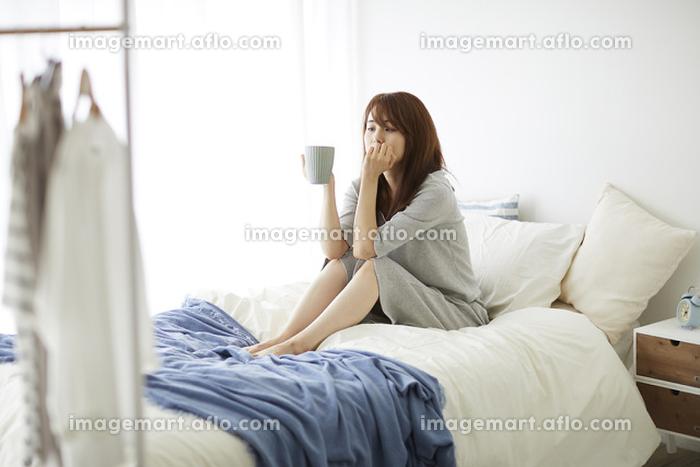 ベッドの上でくつろぐ日本人女性の販売画像