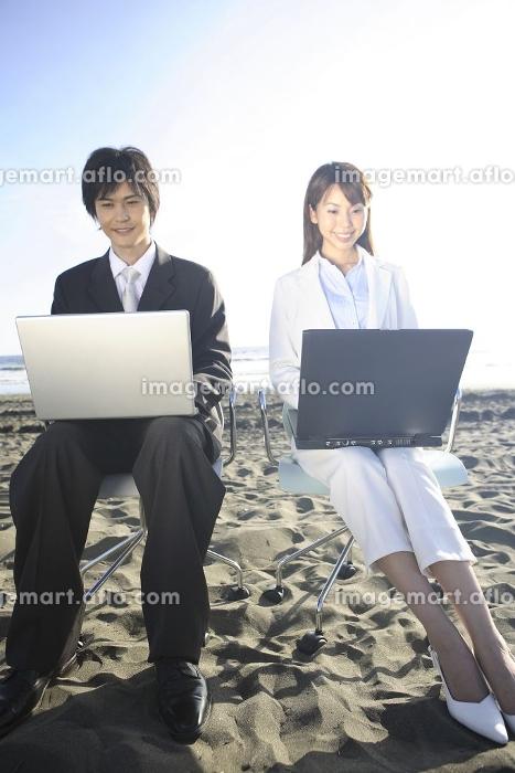砂浜で仕事する男女の販売画像
