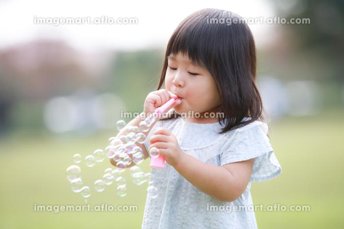 しゃぼん玉で遊ぶ女の子の販売画像