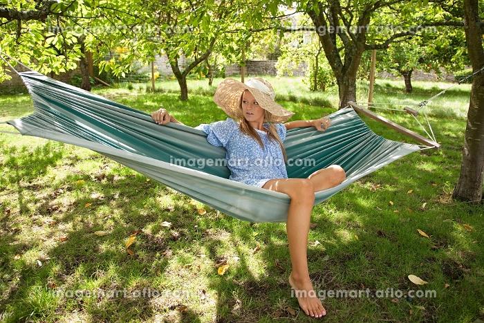 庭でくつろぐ外国人女性の販売画像