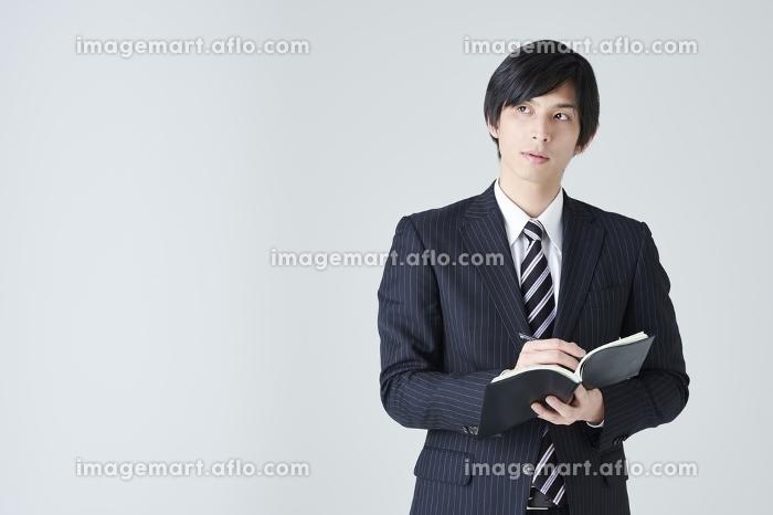 メモを取る日本人ビジネスマンの販売画像