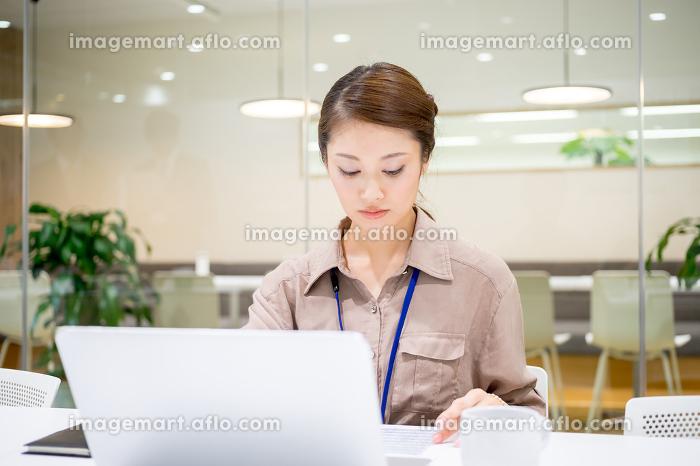 真剣な表情で仕事をする女性(清潔なオフィス)の販売画像