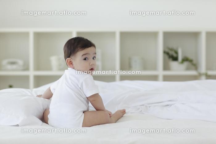 ベッドの上でお座りをして振り返る赤ちゃんの販売画像