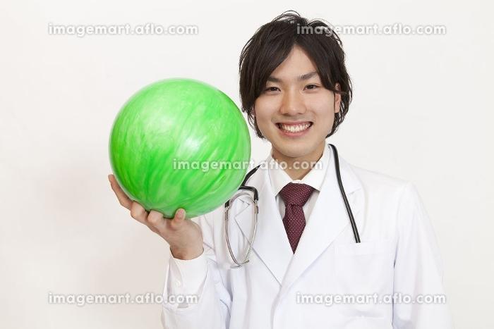 ボウリング球を持って微笑む医師の販売画像