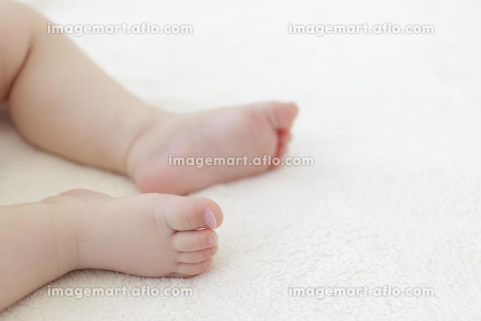 ベッドで眠る赤ちゃんの足の販売画像