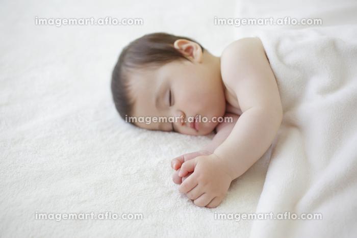 ベッドで眠る赤ちゃんの販売画像
