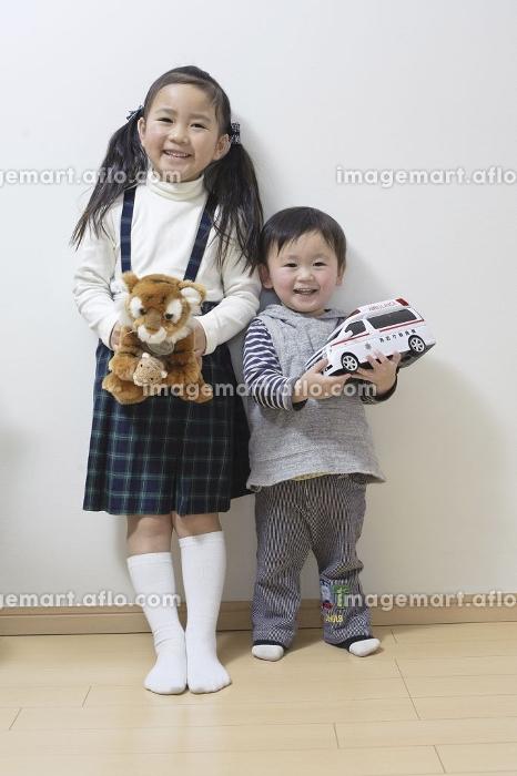 姉弟で仲良くおもちゃを持って並んでパチリの販売画像