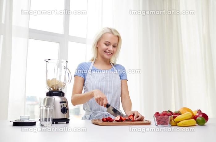 smiling woman with blender preparing shake at homeの販売画像