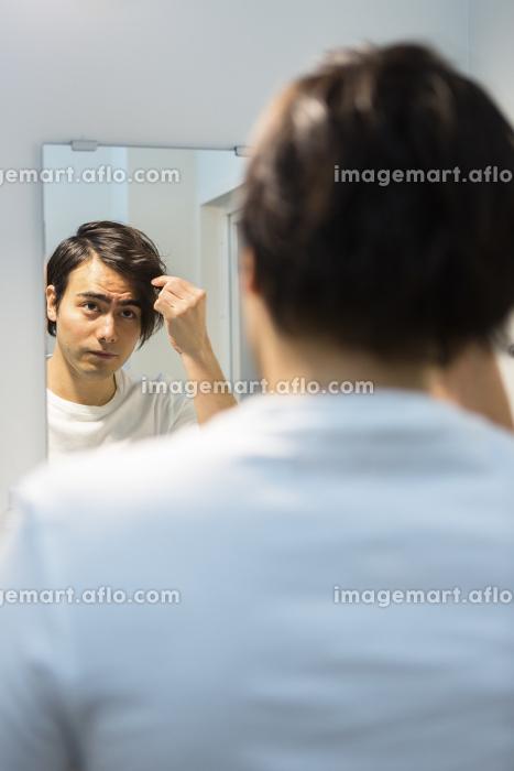 鏡を見る男性の販売画像