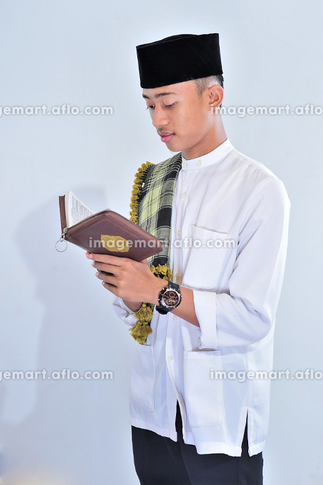 Portrait of handsome young muslim man enjoy reading (tilawat ul quran) a holy Quran in Ramadan , Jakarta, Jakarta, Indonesia