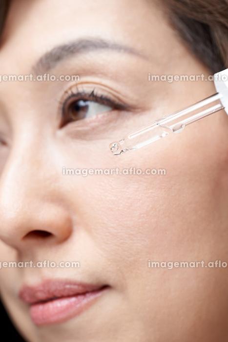 顔に美容液を垂らす中年の日本人女性の販売画像