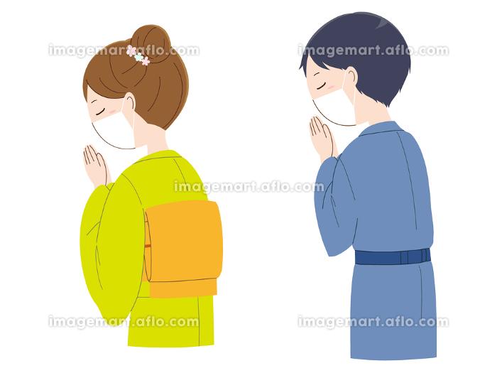 手を合わせ祈るマスクと着物姿の女性と男性の販売画像