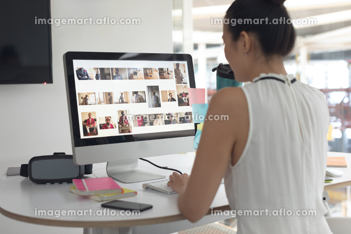 Rear view of Asian female graphic designer drinking water while working on computer at desk in a modern officeの販売画像