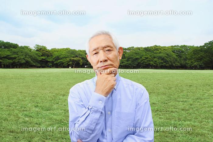 広場で悩んでいるシニアの日本人男性