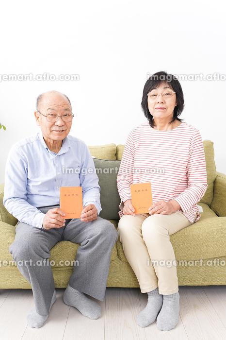 年金手帳を持つ高齢の夫婦の販売画像