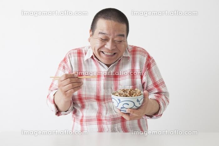 食事を摂る中年男性の販売画像