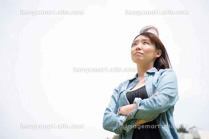 遠くを見上げる女性の販売画像