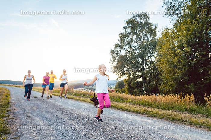 Playful family running and playing on a path in summer landscapeの販売画像