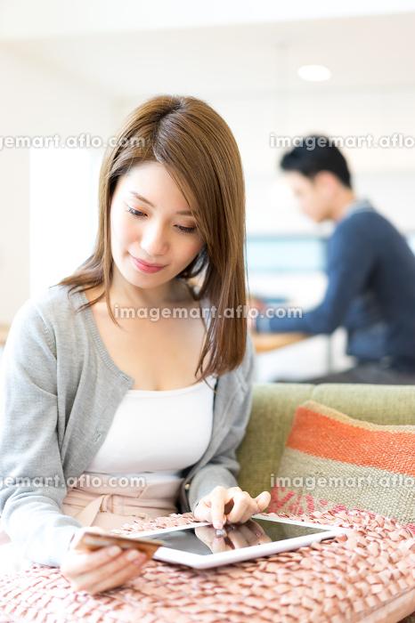 ネットショッピングの決済をする妻(自宅・リビング・ライフスタイル)の販売画像