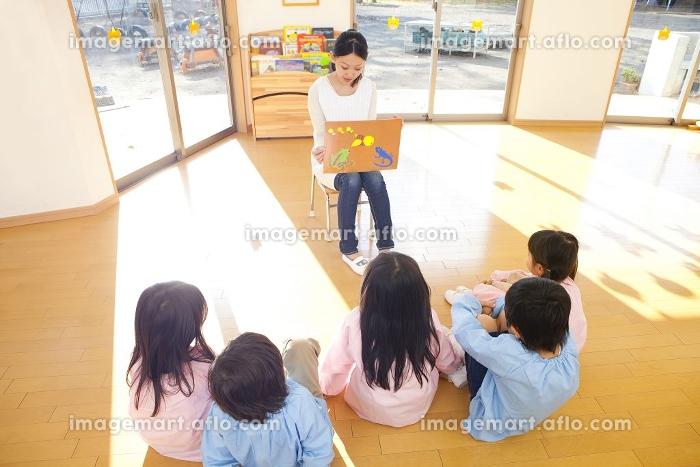 紙芝居に聞き入る幼稚園児5人の後姿の販売画像