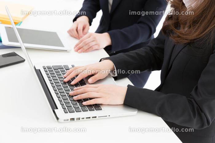 パソコンとタブレットを見る二人の女性の手元 ビジネスの販売画像