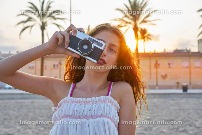 Teen girl with retro photo camera at sunset as a photographerの販売画像