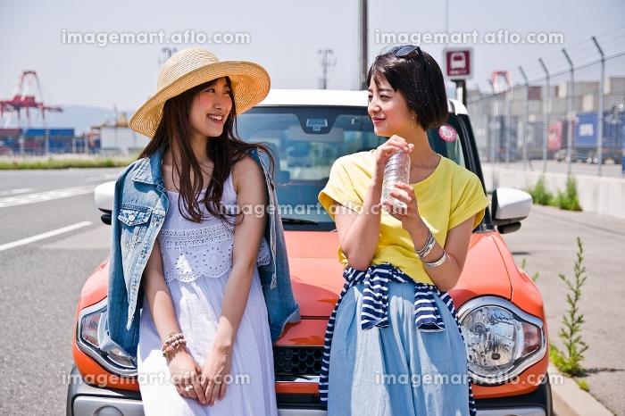 車の前で会話する女性の販売画像