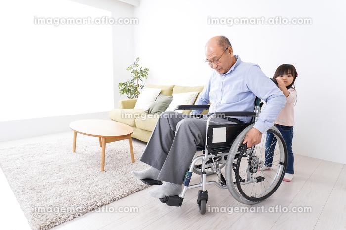 車椅子に乗る高齢男性と女の子の販売画像