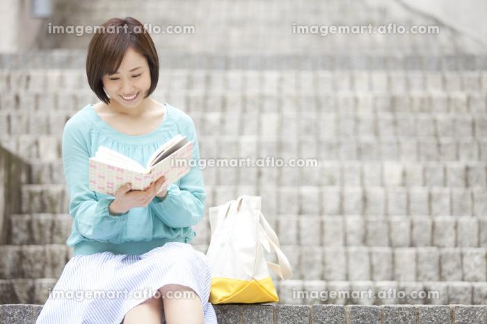 階段で本を読む女性の販売画像