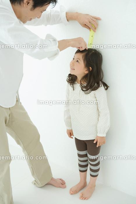 娘の身長を測る父親の販売画像