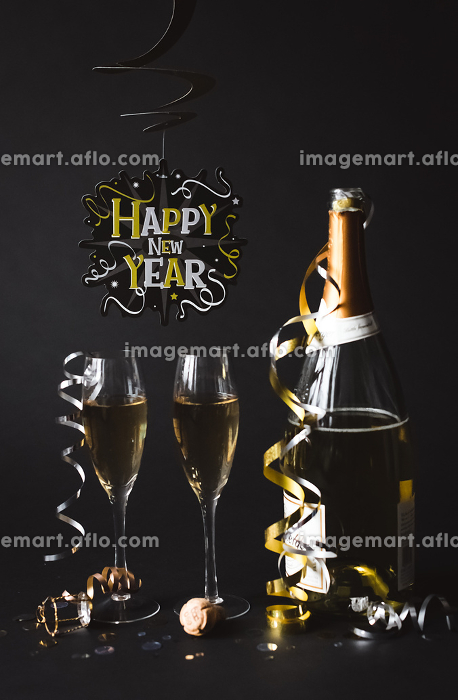 Champagne and Happy New Year sign with black background.の販売画像