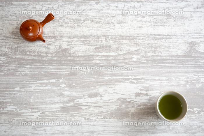 緑茶の入った湯呑みと茶色の急須の背景素材の販売画像