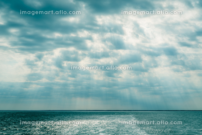 Clouds over the ocean with sunbeams in daylightの販売画像