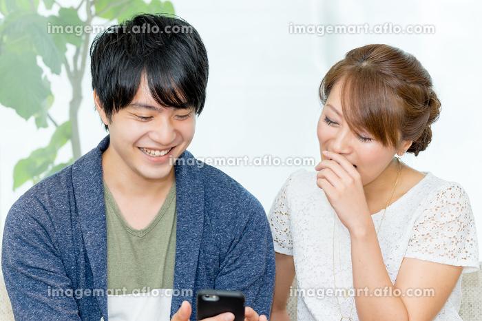 男女でスマートフォンを見る(正面)の販売画像