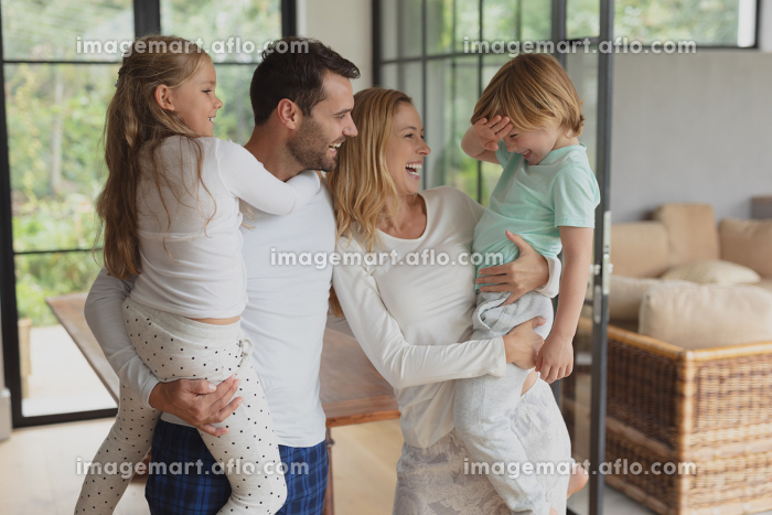 Front view of happy Caucasian parents holding their children at homeの販売画像