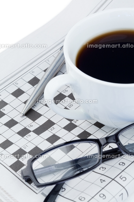 Coffee a pen a pair of glasses and a crossword puzzle on a white backgroundの販売画像