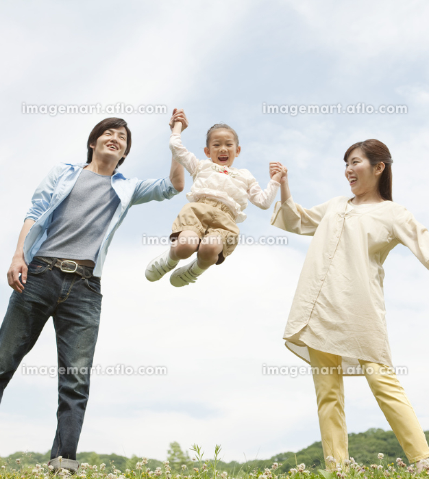 手をつないで遊ぶ家族3人の販売画像