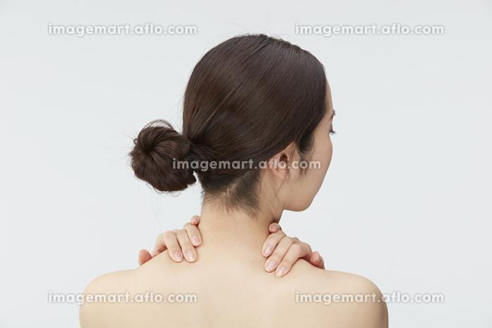 首もとに手をあてる女性の販売画像