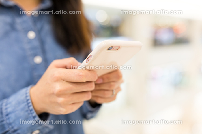 Woman sending sms on mobile phoneの販売画像