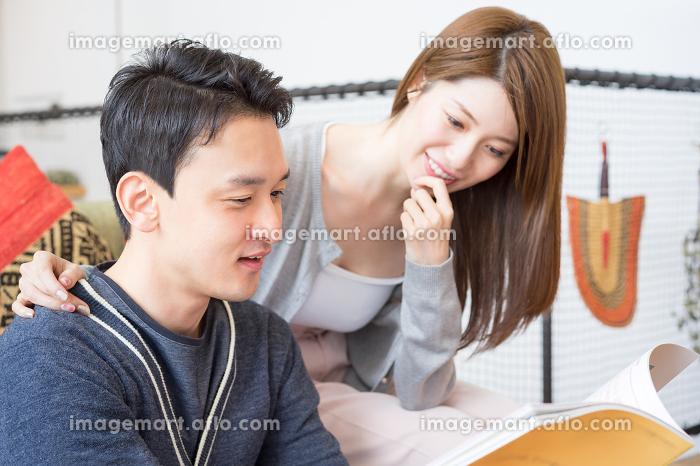 一緒に雑誌を見る仲良しのカップルの販売画像