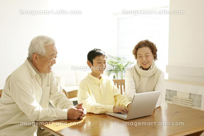 パソコンをする子供と祖父母