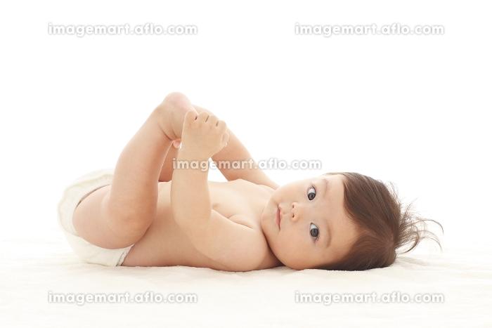 ブランケットの上に寝そべる裸の赤ちゃん