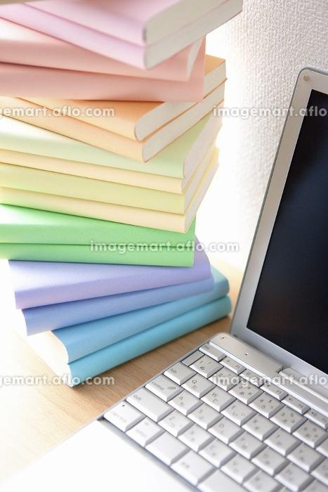 ノートパソコンと積まれた本