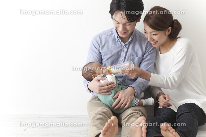 子供にミルクを飲ませる夫婦の販売画像