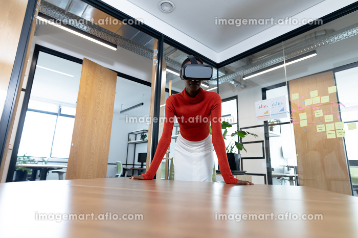 African american businesswoman leaning on desk and using vr headset in meeting room. business in a modern office.の販売画像