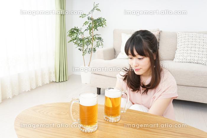 ビールを飲む若い女性の販売画像