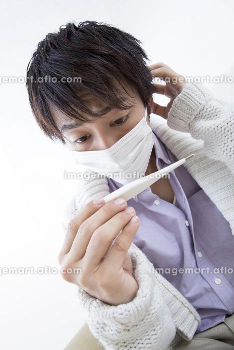 体温計を見て困惑する男性