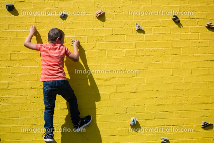 Rear view of boy climbing on yellow wallの販売画像